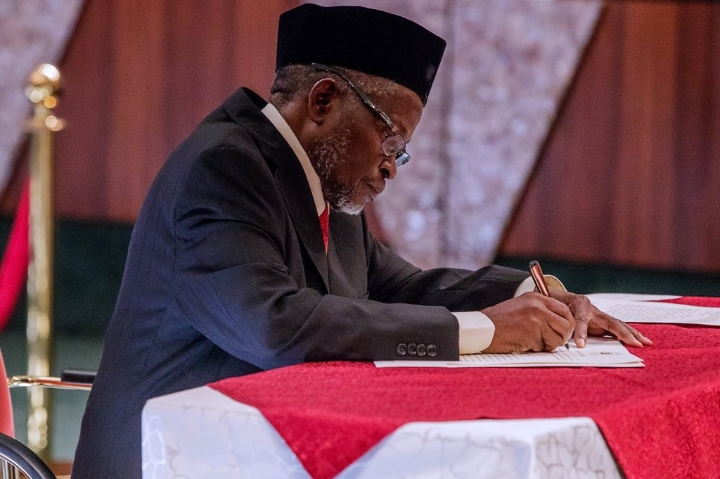 Justice Ibrahim Tanko Mohammad signing his appointment letter