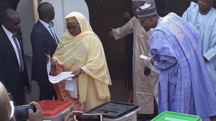 President Muhammadu Buhari spying on the ballot paper of his wife Aisha Buhari during voting in Daura Saturday