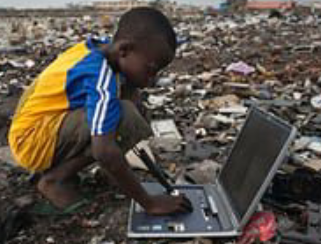 Young African boy playing with scrap laptop in a thrash dump
