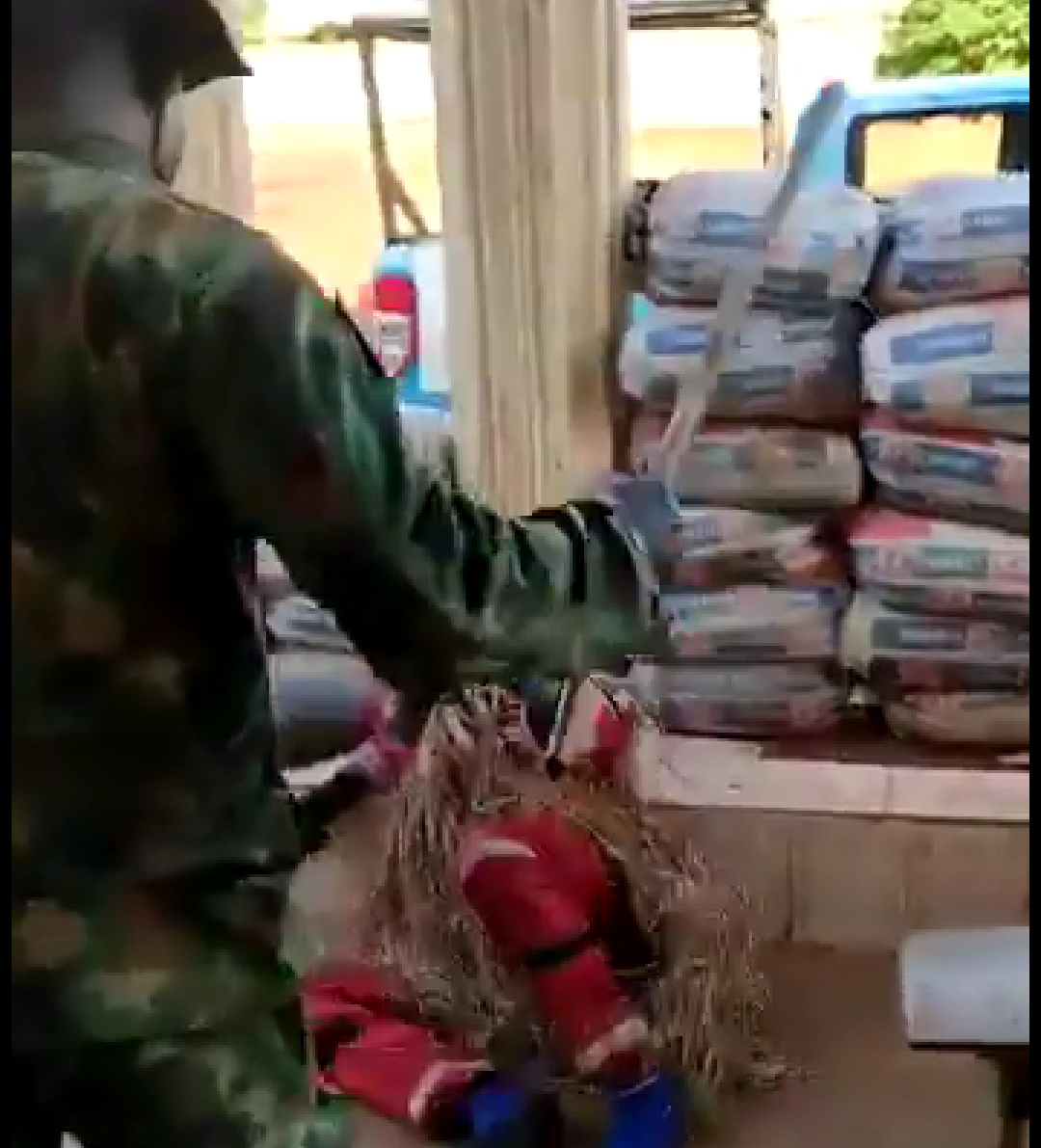 A Soldier beating up a masquerade with a stick